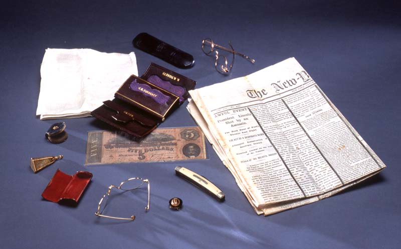 Items found in Lincoln's pockets on the night of his assassination and a newspaper from that time.